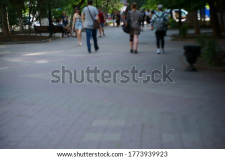 Blurred background. People walk along a city street.