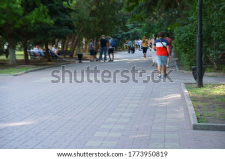Blurred background. People walk in the city Park. Walking.