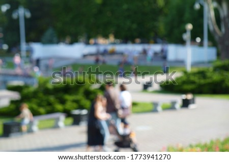Blurred background. People walk in the recreation Park.
