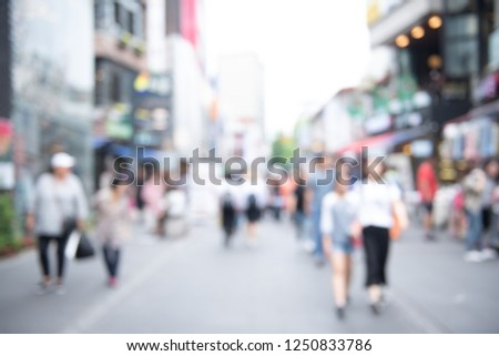 Blurred background, people walking at outdoor street market, business area in the city. Crowd street in Korea. Summer Holiday Shopping #1250833786