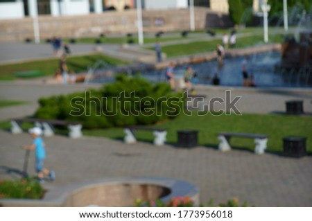 Blurred background. People with children relax in the city Park.