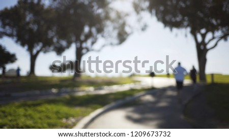 Blurred background plate of sunny park filled with joggers and cyclists #1209673732