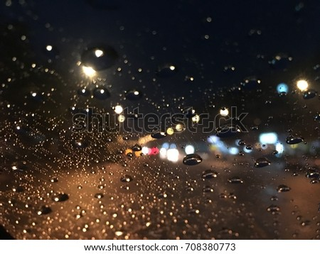 Blurred background, raindrop on the windshield, street light at night on a rainy day. #708380773