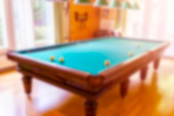 Blurred background snooker billiards on table balls. Billiard bokeh. Blurred Billiard table close up. Billiards balls and cue on green billiards table bokeh background