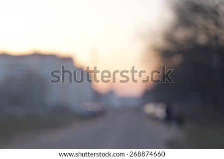 Blurred background: twilight, sunset sky, urban road - houses and park