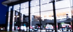 Blurred background with car dealership exterior. Abstract blurred photo of modern building motor showroom. Blur car show room office bokeh lights. Automobile retail shop