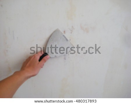 Blurred background with hand holding putty knife patching a hole in a white wall. Renovation repair process indoor.
