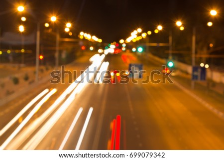 Blurred background with night road and light from the headlights of cars #699079342
