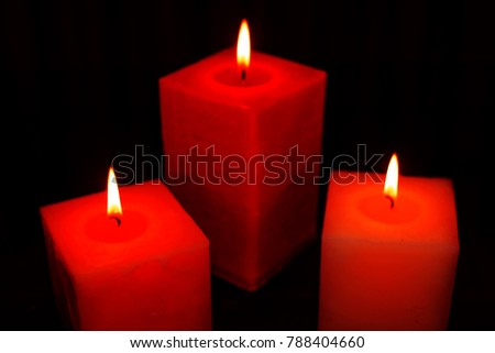 Blurred background with three decorative red candles burning brightly in darkness #788404660