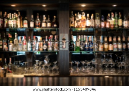 Blurred bar shelves and bar counter with many bottles of liqueurs  #1153489846