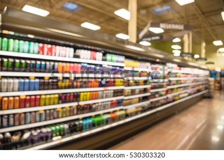 Blurred beverage display on cold freezer at local store in Humble, Texas, US. Variety of cold energy drinks, soft drinks, bottled juice and sport drinks on display. Drink zone aisle concept.