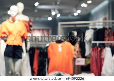 Blurred big sales on Black Friday. On sale at a clothing store in a modern shopping mall. Beautifully laid out things on hangers. Basic background for design