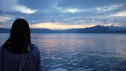 Blurred. Black hair woman standing backwards and watching magical, dreamy and dramatic sunrise over the lake in mountain country landscape. Lonely but beautiful. Blue and pink pastel tone.