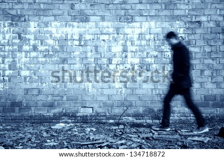 blurred black man walking through a old weathered wall