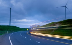 Blurred blades or wind turbine slowly rotating backlit by setting sun and cloudy sky from roadside with light trails of passing petrol engined vehicles