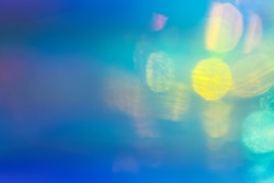 Blurred blue and green abstract lens flare background. Defocused glow effect. Illuminated bokeh