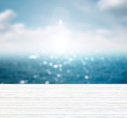 Blurred blue background of sea and sky with free space on wooden table.