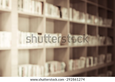 Blurred books on the shelf in public library in vintage color tone for background