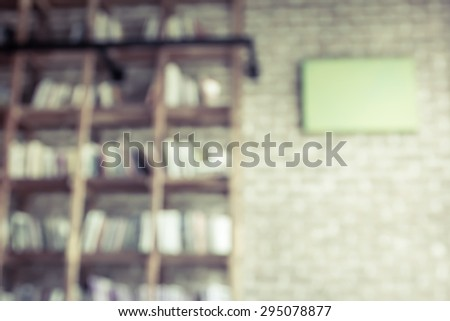 Blurred books on the shelf with brick wall in public library in vintage color tone