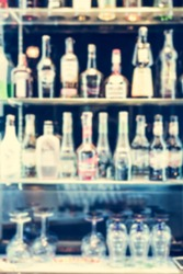 Blurred bottle of alcoholic drinks and glasses are on the shelf for background