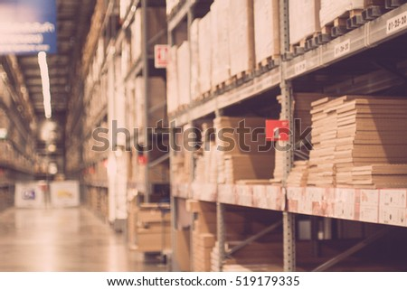 Blurred boxes on rows of shelves in warm light warehouse background.