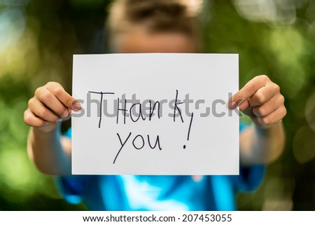 Blurred boy holding a piece of paper with the words Thank You in front of her.