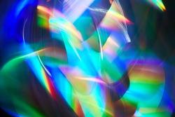 Blurred bright rainbow light. Lens or prism dynamic flare. Draving shiny spots. Dark background. Illuminated burst of multicolor light.