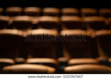 blurred brown special leather seat in movie theater. pattern of many armchairs in dark room .