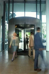 Blurred business people in revolving door of lobby