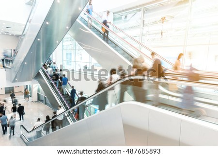 Blurred business people on a escalator, germany