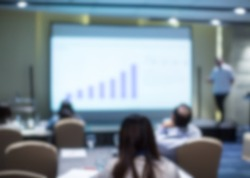 Blurred business presentation with corporate speaker near blank white screen. Seminar concept background with executive leading workshop in conference hall. Presenter in lecture to audience.