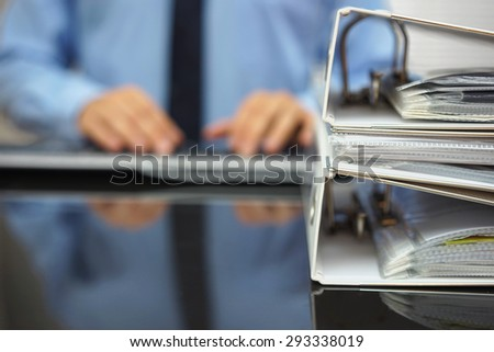 blurred businessman is typing on computer keyboard with documentation in focus