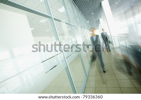 Blurred businesspeople moving in the corridor