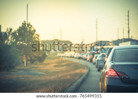 Blurred busy road long line of cars waiting at stop light in Houston, Texas, USA. Rear view red car brake. Typical traffic jam, rows of cars stopping on road during rush hour at sunset. Vintage tone