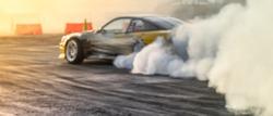 Blurred car drifting on asphalt racing track with lot of smoke, motion blur drift car.