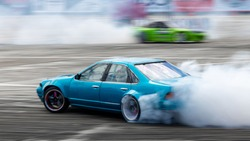 Blurred car drifting, Two car drifting battle on asphalt street road race track, Automobile and automotive drift car with smoke from burning tire on speed track.