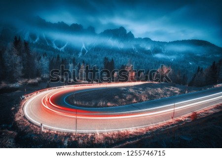 Blurred car headlights on winding road in mountains with low clouds at night in autumn. Moody landscape with asphalt road, light trails, foggy forest, rocks and blue sky at dusk. Roadway in Italy #1255746715