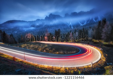 Blurred car headlights on winding road in mountains with low clouds at night in autumn. Spectacular landscape with asphalt road, light trails, foggy forest, rocks and blue sky. Car driving on roadway