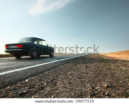 Blurred car on an asphalt road and blue sky with clouds