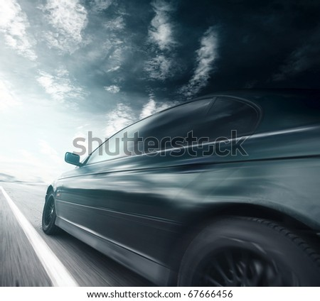 Blurred car on asphalt road and sky with clouds