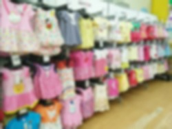 Blurred childrens undershirts on clothes hangers at a store.