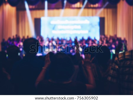 Blurred Christian Congregation Worship God together in Church hall in front of music stage and light effected.