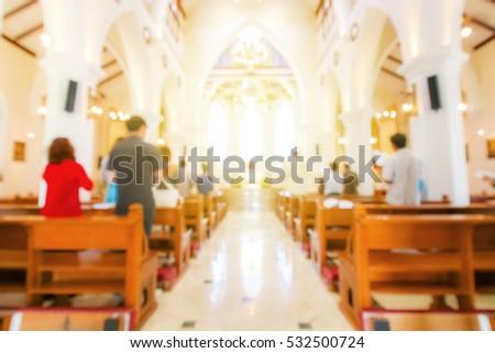 blurred christian mass praying inside the church