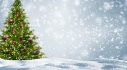 blurred christmas tree in snowy landscape, beautiful abstract winter background with snowflake as xmas concept