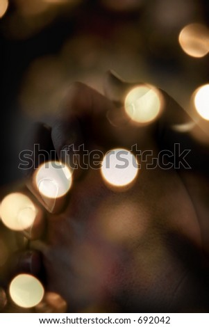 Blurred Christmas tree lights with praying hands blended into image - represents faith and spirituality in the Christmas/Holiday season.