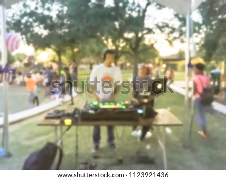 Blurred close-up of DJ mixing music on DJ performance controller with integrated laptop stand. DJ mixing track at local event in Irving, Texas, USA. Music festival and entertainment concept #1123921436