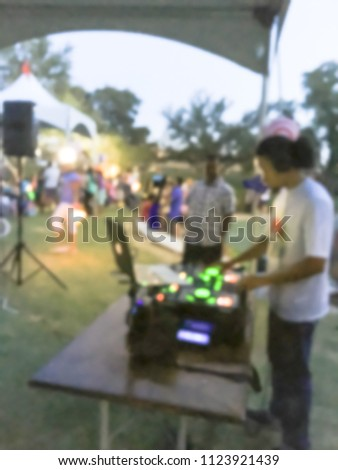Blurred close-up of DJ mixing music on DJ performance controller with integrated laptop stand. DJ mixing track at local event in Irving, Texas, USA. Music festival and entertainment concept #1123921439
