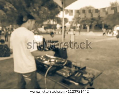 Blurred close-up of DJ mixing music on DJ performance controller with integrated laptop stand. DJ mixing track at local event in Irving, Texas, USA. Music festival and entertainment concept #1123921442