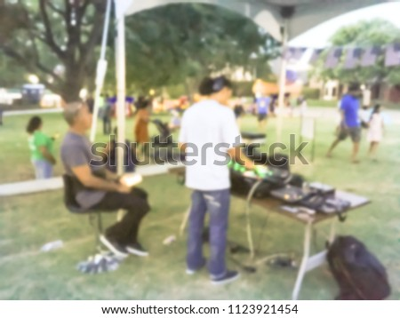 Blurred close-up of DJ mixing music on DJ performance controller with integrated laptop stand. DJ mixing track at local event in Irving, Texas, USA. Music festival and entertainment concept #1123921454