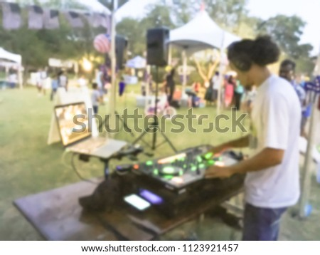Blurred close-up of DJ mixing music on DJ performance controller with integrated laptop stand. DJ mixing track at local event in Irving, Texas, USA. Music festival and entertainment concept #1123921457